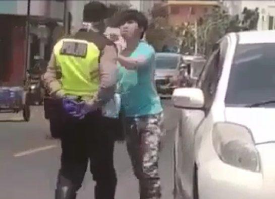 Oknum polisi yang diduga pungli dan ludahi pengendara mobil berpakaian biru (Foto: Screenshot video)