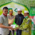 Rais Syuriyah Pengurus Cabang Nahdatul Ulama (PCNU) kota Makassar AGH. Baharuddin HS serahkan zakat fitrah secara simbolis kepada mustahiq (Foto:Ist)