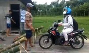 Pengendara motor saat ingin melintas namun dihadang oleh warga dengan meriam bambu, terpaksa putar balik (Foto: screenshot fakta.indo)